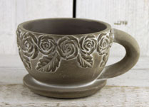 Whitewashed Oval Stone Teacup and Saucer with Rose Design