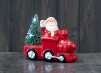 Novelty Santa on red train with LED Christmas tree.