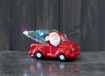 Novelty Santa on red truck with LED Christmas tree.