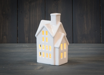 White ceramic house with internal battery-powered LED lights.